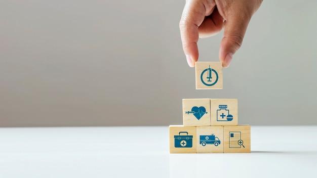 Icône de handon d'affaires sur le bloc de cube en bois et l'icône médicale