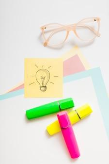 Icône d'idée sur une note adhésive avec marqueur de surbrillance; lunettes et papier cartonné sur fond blanc