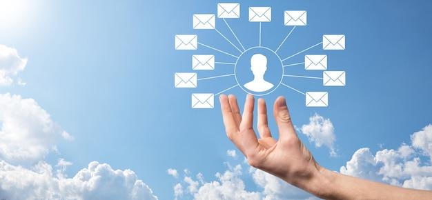Icône de lettre tenant une main masculine, icônes de courrier électronique. contactez-nous par courrier électronique et protégez vos informations personnelles contre les courriers indésirables. centre d'appels du service client contactez-nous. marketing par e-mail et newsletter