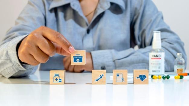 L'icône médicale sur le bloc de cube en bois et l'icône de sac de médecine cueillie à la main