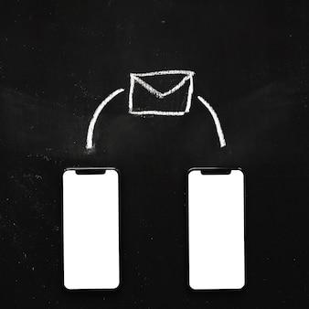 Icône de message dessiné sur les deux téléphone portable vide sur tableau noir