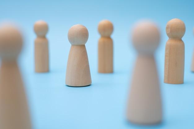 Icône de personnes en bois interconnectées par des lignes blanches sur fond bleu.