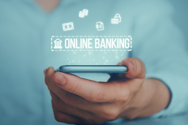 Icônes abstraites de la banque en ligne sur la main avec smartphone.