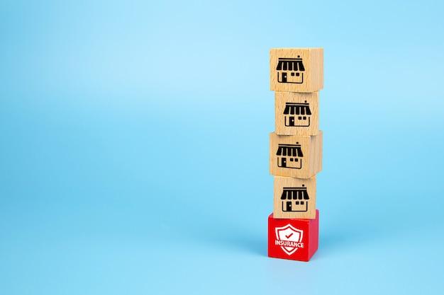 Icônes de marketing de franchise le magasin sur le blog de jouets en bois cube est empilé avec une base d'icônes d'assurance.