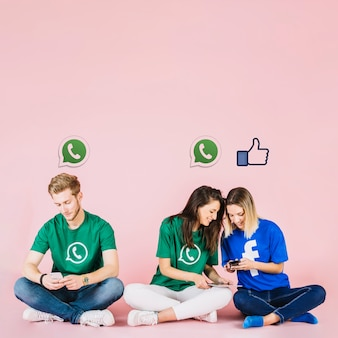 Icônes de médias sociaux sur le groupe d'amis à l'aide de téléphone portable