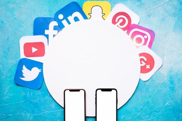 Icônes de médias sociaux vives sur le cadre circulaire avec deux téléphone portable sur le mur bleu