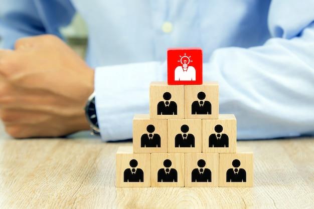 Icônes de personnes sur des blocs de jouets en bois cube empilés.