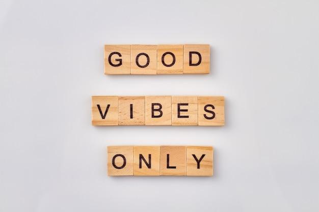 Idée abstraite de bonnes vibrations. construction de phrase de motivation avec des cubes en bois. isolé sur fond blanc.