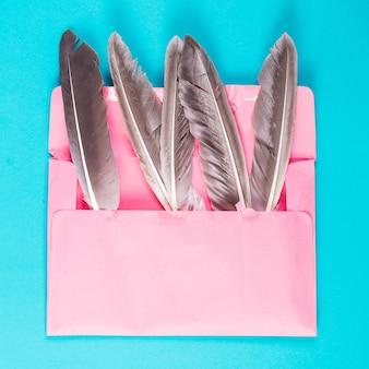 Idée cinq plumes dans une enveloppe rose. minimalisme