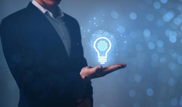 Idée et concept d'équipement. homme d'affaires main tenant ampoule et rouage à l'intérieur.