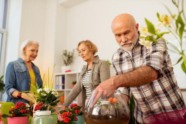 Idée d'empotage. bel homme beau regardant le vase transparent avec sol tout en étant engagé dans le travail