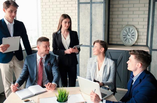 Idée de génie. groupe de gens d'affaires regardant l'ordinateur portable ensemble. une femme d'affaires regardant la caméra