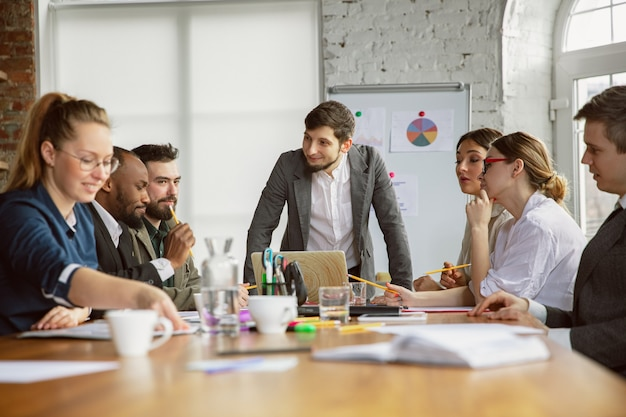 Idée de génie. groupe de jeunes professionnels ayant une réunion. un groupe diversifié de collègues discute de nouvelles décisions, plans, résultats, stratégie. créativité, lieu de travail, affaires, finance, travail d'équipe.