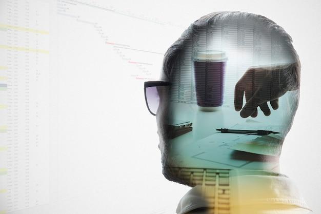 L'idée de l'image de l'analyste. double exposition de la tête d'un homme travaillant avec des données.
