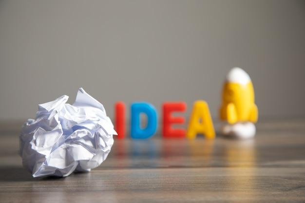 Idée de lettrage, papier froissé et fusée sur la table