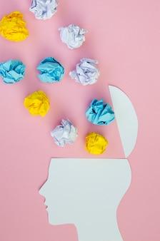 Idée métaphorique avec tête et papiers froissés