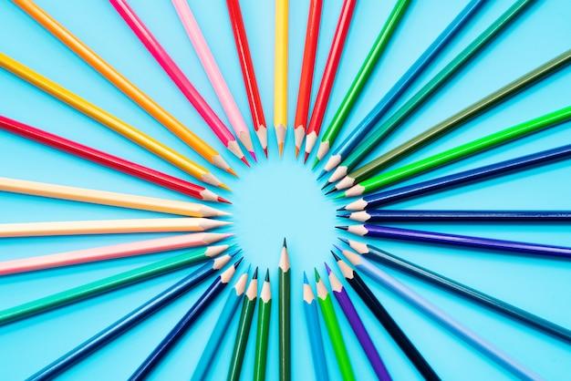 Idée partage concept, crayons multicolores sur fond bleu