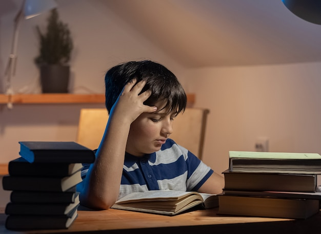 Idée de la participation d'un enfant à l'apprentissage du visage concentré d'un garçon lisant un livre dans sa chambre