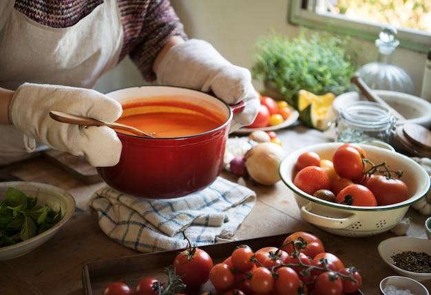Une idée de recette de photographie de nourriture de femme au foyer faisant cuire la sauce tomate