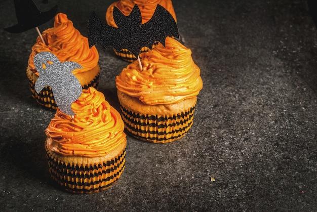 Idée simple de gâterie drôle pour enfant pour halloween: gâteaux à la citrouille à la crème, avec des décorations en forme de symboles de vacances - fantôme, sorcière, chauve-souris. sur un fond noir, copyspace