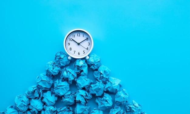 Idée de synchronisation et de réflexion avec boule de papier froissé et horloge blanche