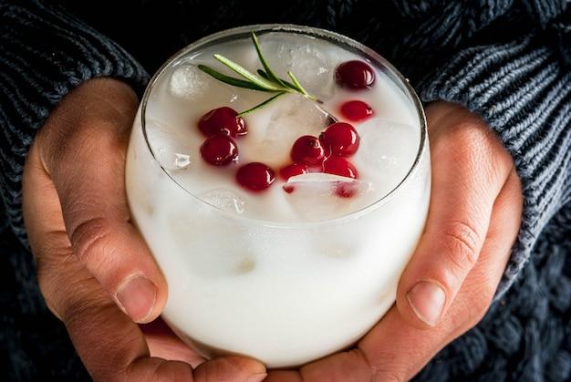 Idées de boissons pour noël et action de grâces. mains féminines avec punch de noël blanc margarita aux canneberges et au romarin, confortable, vue rapprochée,