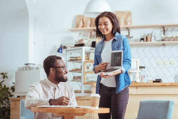 Des idées fraîches. belle jeune femme tenant un ordinateur portable et donnant une présentation sur le concept de projet à son collègue masculin dans le café