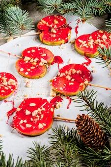 Idées d'hiver, gâteries de noël. bonbons pour les enfants. tranches de pomme au chocolat au caramel rouge et noix. fond de pierre grise, avec des branches d'arbres de noël, vue de dessus copie espace