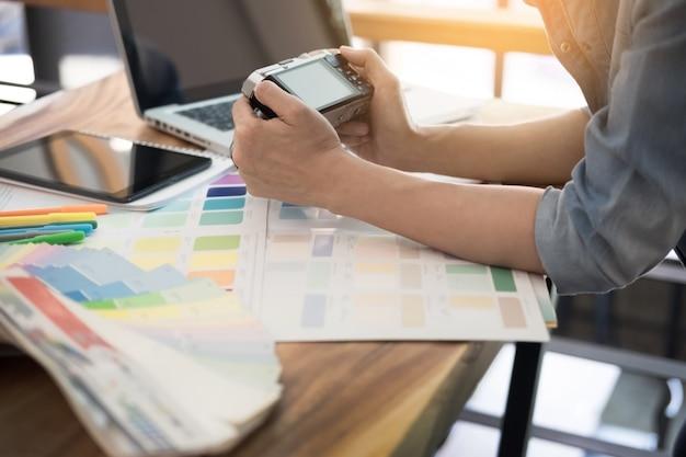 Idées de photographie profession créative design studio concept, photographe féminin assis sur le bureau avec un ordinateur portable