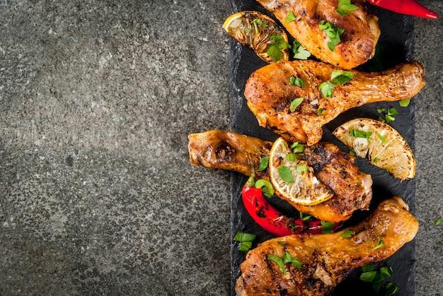 Idées de plats d'été pour le barbecue grillades ailes de cuisses de poulet grillées frites sur le feu avec du piment fort citron et sauce barbecue table en pierre sombre