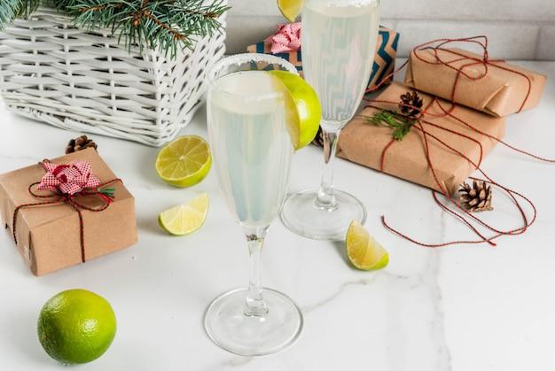 Idées pour les boissons de noël et du nouvel an. cocktails champagne margarita, garnis de citron vert et sel
