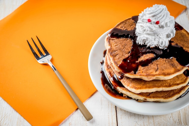 Idées pour le petit-déjeuner des enfants, des friandises pour thanksgiving et halloween. crêpes à la sauce au chocolat et crème fouettée en forme de fantôme. sur une table en bois blanc, copyspace