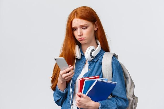 Idiot triste et sombre moue fille aux cheveux rouge foxy, fronçant les sourcils en soupirant et en regardant avec regret l'écran du smartphone