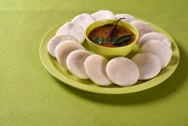 Idli avec sambar dans un bol sur une surface verte, plat indien: nourriture préférée du sud de l'inde rava idli ou semoule paresseusement ou rava paresseusement, servi avec sambar et chutney de noix de coco verte.