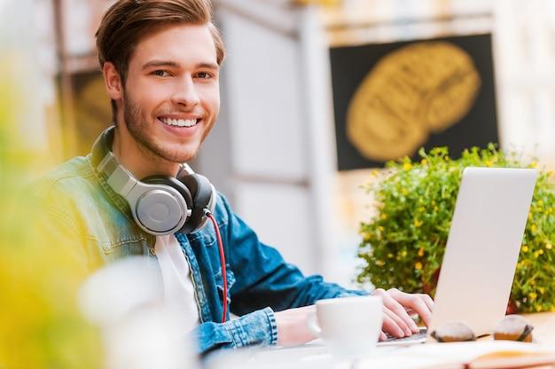 Il aime tellement passer sa journée. heureux jeune homme travaillant sur ordinateur portable et souriant à la caméra