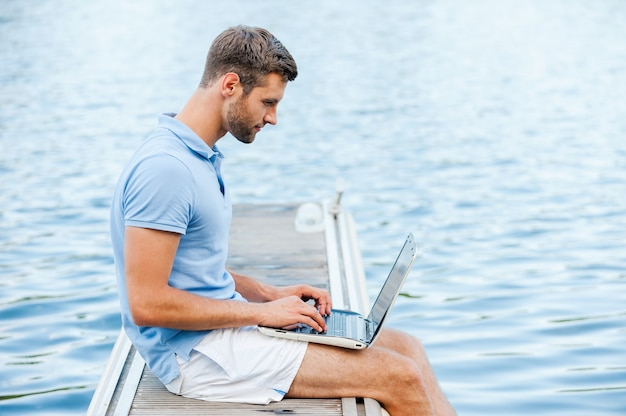 Il aime travailler à l'extérieur. vue latérale du beau jeune homme en polo travaillant sur ordinateur portable alors qu'il était assis sur le quai