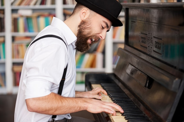 Il a une âme créative. beaux jeunes hommes barbus jouant du piano et chantant