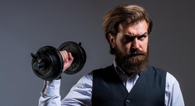 Il est fort. hipster mature brutal en costume avec haltère. affaires et sport. exprimer le vrai pouvoir. être fort dans les affaires et la vie. mâle réussi avec barbe et moustache. homme d'affaires tenir des haltères.