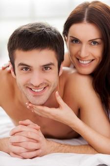 Il est à moi! joyeux jeune couple d'amoureux allongé dans son lit et souriant pendant que la femme touche le menton de son petit ami