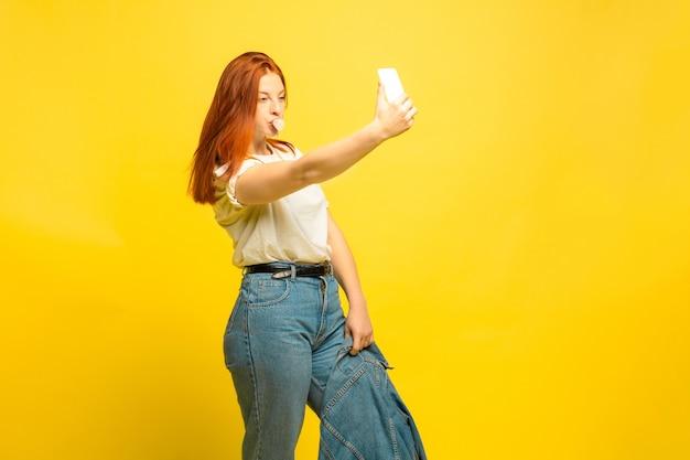 Il est plus facile d'être suiveur. besoin de vêtements minimum pour selfie. portrait de femme caucasienne sur fond jaune. beau modèle de cheveux roux féminin. concept d'émotions humaines, expression faciale, ventes, publicité.