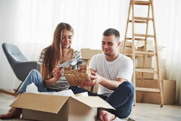 Il est temps de déballer ces boîtes. joyeux jeune couple dans leur nouvel appartement. conception du déménagement.
