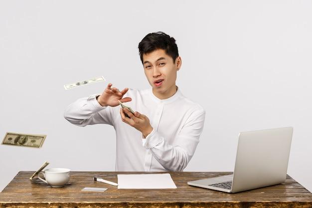 Il est temps de faire la fête. jeunes entrepreneurs chinois riches et prospères insouciants, jetant de l'argent avec une expression ravie impertinente, gaspillant de l'argent, jouant avec des dollars