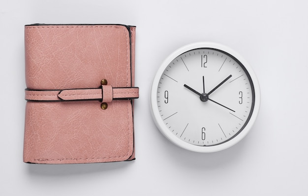 Il est temps de gagner de l'argent. horloge blanche et portefeuille sur fond blanc. tourné en studio minimaliste. vue de dessus
