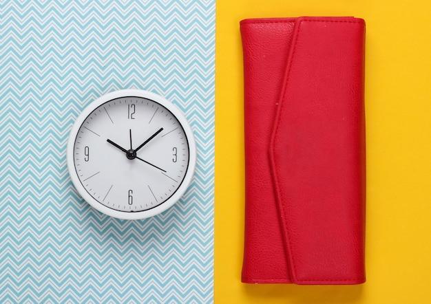 Il est temps de gagner de l'argent. horloge blanche et portefeuille sur fond bleu jaune. tourné en studio minimaliste. vue de dessus