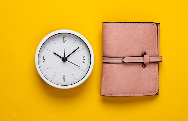 Il est temps de gagner de l'argent. horloge blanche et portefeuille sur fond jaune. tourné en studio minimaliste. vue de dessus