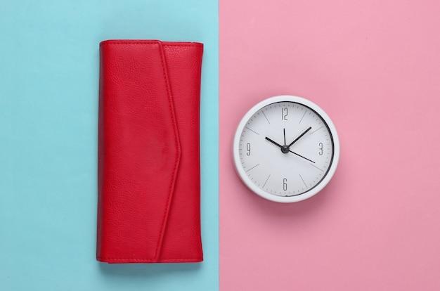 Il est temps de gagner de l'argent. horloge blanche et portefeuille rouge sur fond rose pastel. tourné en studio minimaliste. vue de dessus