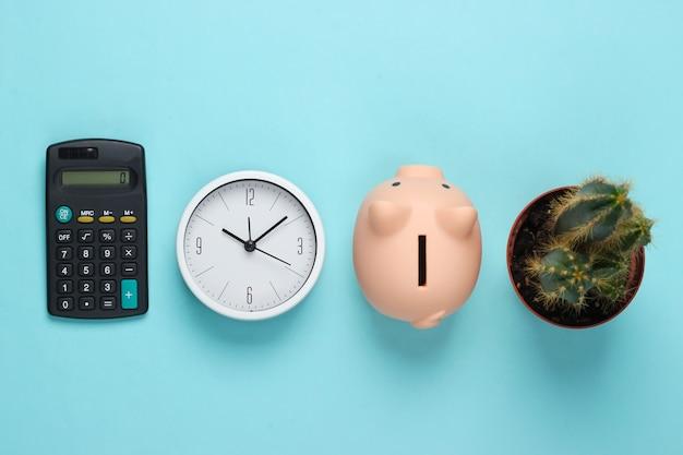 Il est temps d'investir. horloge blanche et tirelire, calculatrice, cactus sur fond bleu. tourné en studio minimaliste. vue de dessus