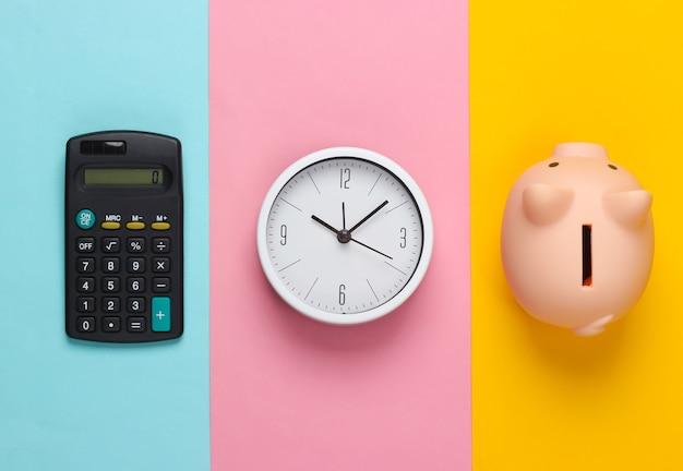 Il est temps d'investir. horloge blanche et tirelire, calculatrice sur fond coloré. tourné en studio minimaliste. vue de dessus