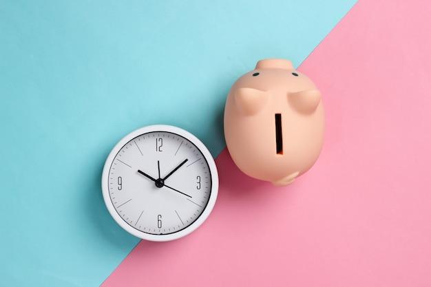 Il est temps d'investir. horloge blanche et tirelire sur fond pastel bleu rose. tourné en studio minimaliste. vue de dessus