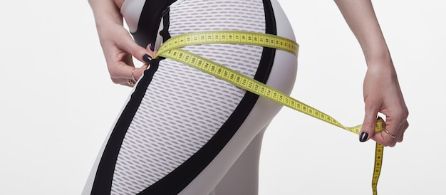 Il est temps pour un régime minceur de perdre du poids. fitness femme fit fille sportswear avec ruban à mesurer mesurant sa cuisse sur blanc